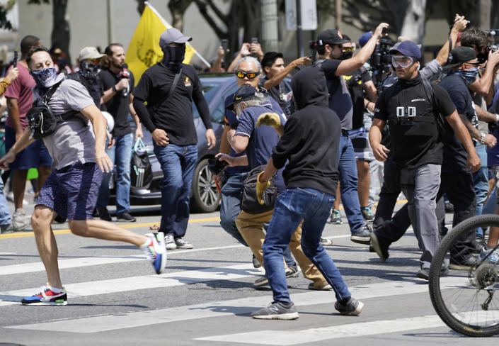 Anti-vaccination demonstrators left, clash with counter-protesters during an anti-vaccination protest in front of the City Hall in Los Angeles on Saturday, Aug. 14, 2021. A man was stabbed and a reporter was attacked Saturday at a protest against vaccine mandates on the south lawn of Los Angeles' City Hall after a fight broke out between the protesters and counter-protesters, the Los Angeles Police Department and local media said. (AP Photo/Damian Dovarganes)