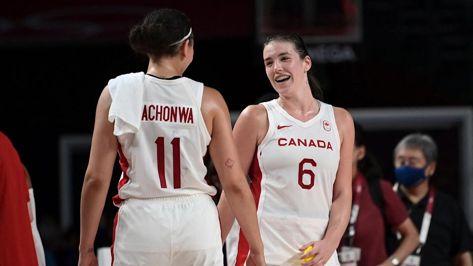 Canada's Natalie Achonwa and Bridget Carleton react after their victory.  (Photo by Aris MESSINIS / AFP)