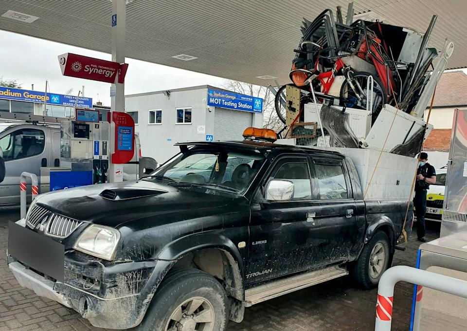Police were left stunned after pulling over this dangerously overloaded pick-up truck which was piled high with a mountain of rubbish held together by pieces of rope. (SWNS)