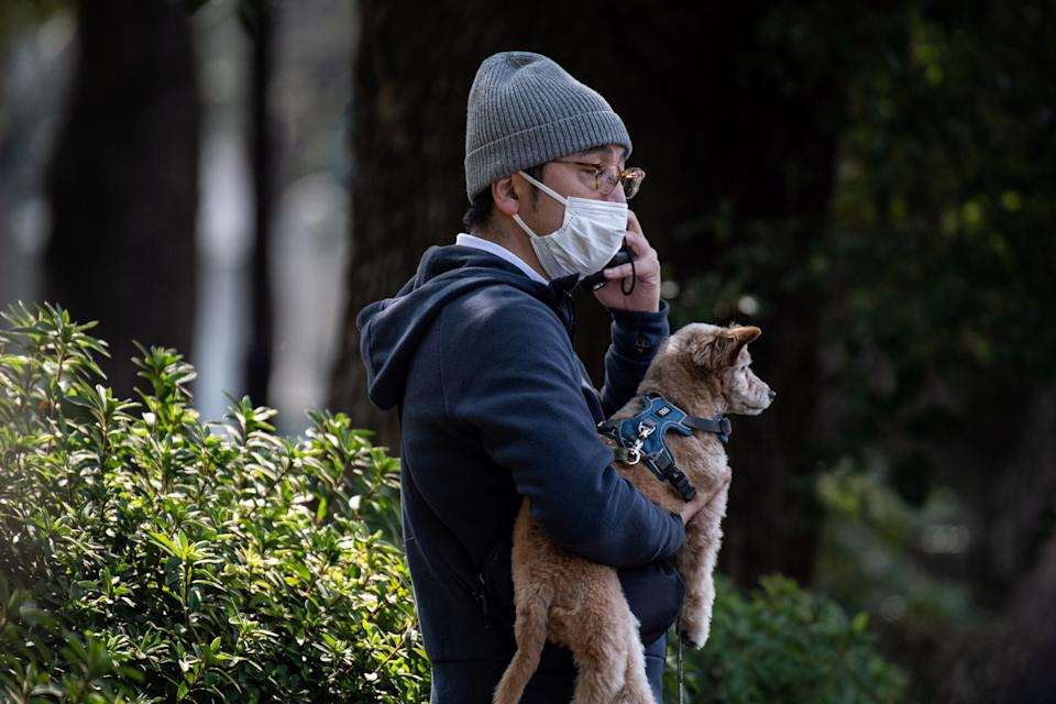 A spectator wearing a face mask watches the Tokyo Marathon with his dog in Tokyo.