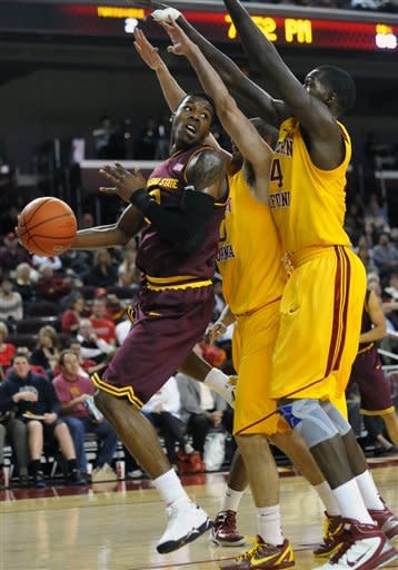 Arizona State forward Carrick Felix, left, looks to pass around Southern California defenders Eric Strangis, center, and Dewayne Dedmon (14) during the first half of an NCAA college basketball game, Thursday, Jan. 5, 2012, in Los Angeles. (AP Photo/Richard Hartog)