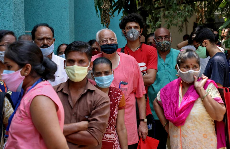 <p>People wearing protective face masks wait to receive a vaccine against Covid-19 at a vaccination centre in Mumbai, India, on 28 April </p> (Reuters)