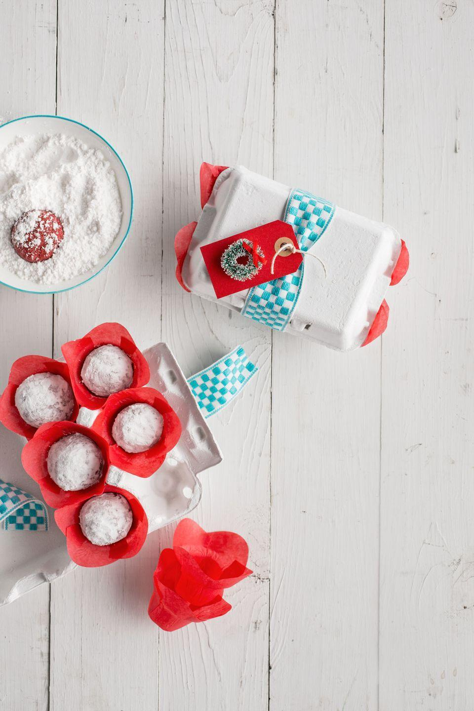 """<p>After whipping up these snowball treats, fill a six-egg carton with mini lotus cupcake liners and add cookies. Tie it up with a plain tag adorned with a bottle brush wreath.</p><p><strong><a href=""""https://www.countryliving.com/food-drinks/recipes/a36895/red-velvet-snowballs/"""" rel=""""nofollow noopener"""" target=""""_blank"""" data-ylk=""""slk:Get the recipe"""" class=""""link rapid-noclick-resp"""">Get the recipe</a>.</strong></p><p><a class=""""link rapid-noclick-resp"""" href=""""https://go.redirectingat.com?id=74968X1596630&url=https%3A%2F%2Fwww.papermart.com%2Flotus-cupcake-baking-cups%2Fid%3D36817&sref=https%3A%2F%2Fwww.countryliving.com%2Ffood-drinks%2Fg647%2Fholiday-cookies-1208%2F"""" rel=""""nofollow noopener"""" target=""""_blank"""" data-ylk=""""slk:SHOP LOTUS CUPCAKE LINERS"""">SHOP LOTUS CUPCAKE LINERS</a><br></p>"""