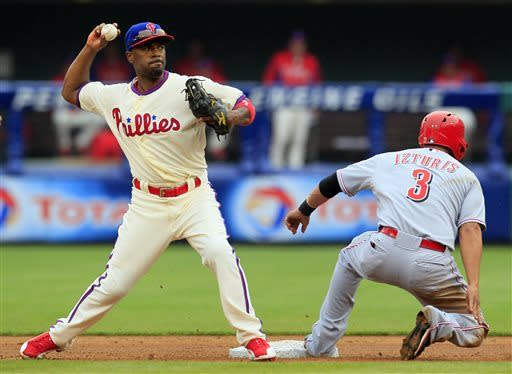 Cincinnati Reds' Cesar Izturis (3) is forced out at second as Philadelphia Phillies' Jimmy Rollins throws to first to complete the double play during the third inning of a baseball game on Sunday, May 19, 2013, in Philadelphia. (AP Photo/Tom Mihalek)
