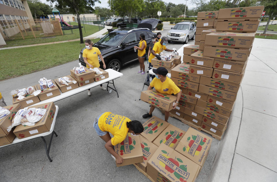 Volunteers load groceries into cars during a food distribution event, Tuesday, July 21, 2020, at St. Monica's Catholic Church in Miami Gardens, Fla. (AP Photo/Wilfredo Lee)