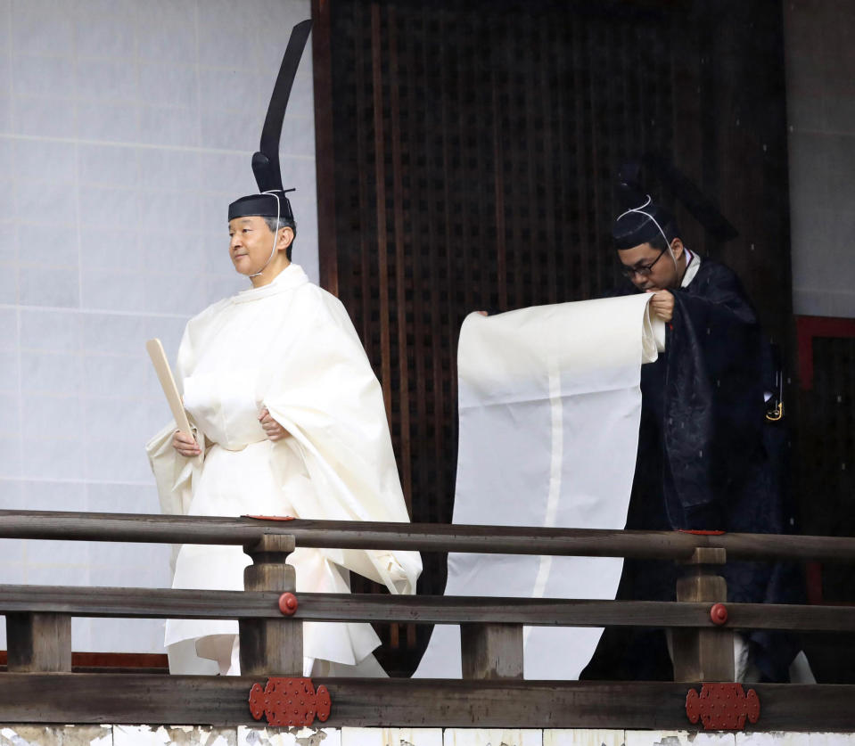 """Japan's Emperor Naruhito, in a white robe, visits """"Kashikodokoro"""", a shrine at the Imperial Palace, in Tokyo, Tuesday, Oct. 22, 2019. Emperor Naruhito visited three Shinto shrines at the palace before proclaiming himself Japan's 126th emperor in an enthronement ceremony. (Kyodo News via AP)"""