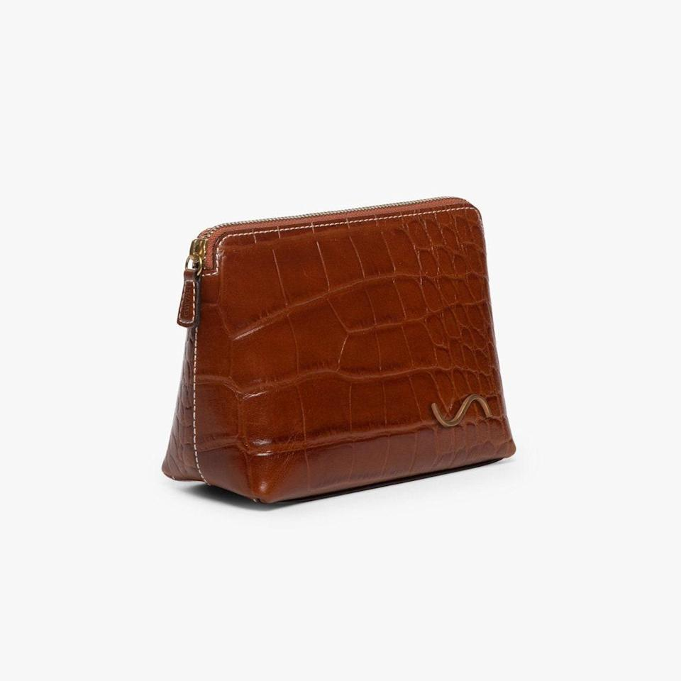 """Staud launched a line of handbags, leather accessories, and shoes a few years ago, and its croc-embossed pouch doesn't disappoint. Use this little number to stash your night-out essentials. (There's even enough room for lipstick.) $125, Staud Clothing. <a href=""""https://staud.clothing/products/makeup-pouch-geranium-croc-embossed?variant=37403637547181"""" rel=""""nofollow noopener"""" target=""""_blank"""" data-ylk=""""slk:Get it now!"""" class=""""link rapid-noclick-resp"""">Get it now!</a>"""
