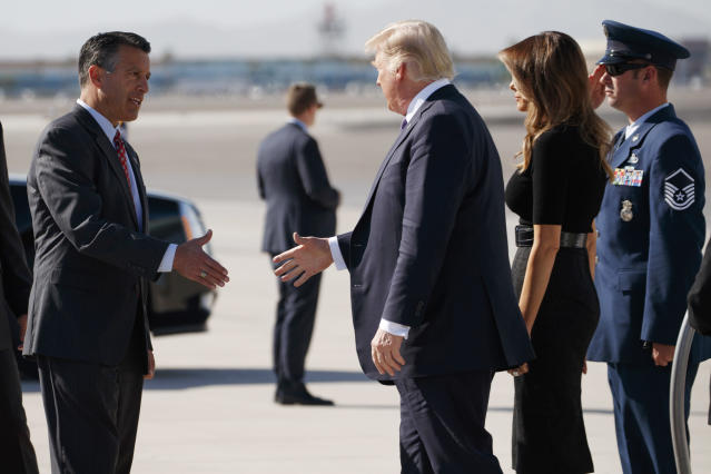 <p>Nevada Gov. Brian Sandoval, left, greets President Donald Trump and first lady Melania Trump as they arrive Wednesday, Oct. 4, 2017, at Las Vegas McCarran International Airport to meet with victims and first responders of the mass shooting. (Photo: Evan Vucci/AP) </p>