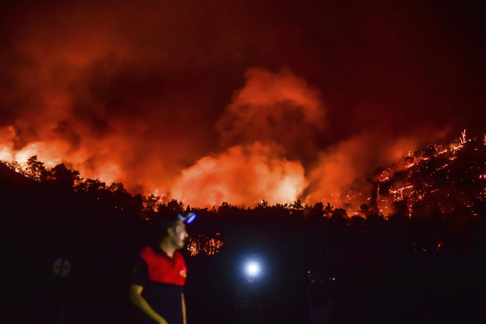 A man leaves as advancing fires rage the Hisaronu area, Turkey, Monday, Aug. 2, 2021. For the sixth straight day, Turkish firefighters battled Monday to control the blazes that are tearing through forests near Turkey's beach destinations. Fed by strong winds and scorching temperatures, the fires that began Wednesday have left eight people dead. Residents and tourists have fled vacation resorts in flotillas of small boats or convoys of cars and trucks. (AP Photo)