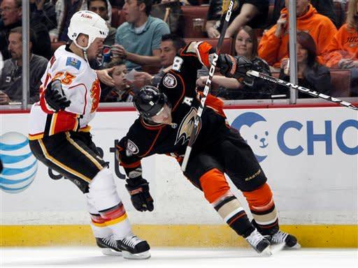 Calgary Flames defenseman Scott Hannan (23) is called for an interference penalty against Anaheim Ducks right wing Teemu Selanne (8) in the second period of an NHL hockey game in Anaheim, Calif., on Friday, March 2, 2012. (AP Photo/Christine Cotter)