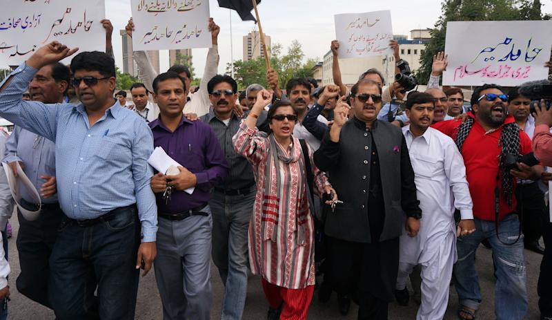 "Pakistani journalists protest for their colleague Hamid Mir, who was shot and injured by gunmen in Karachi on Saturday, Monday, April 21, 2014 in Islamabad, Pakistan. Police in Pakistan said gunmen shot a famous television talk show host amid a wave of attacks on journalists in the country. Police say Hamid Mir, a host on the private television broadcaster Geo, was wounded in the attack Saturday, April 19, 2014, near Karachi's airport. Placard on right reads ""we salute Hamid Mir for his courage."" (AP Photo/B.K. Bangash)"