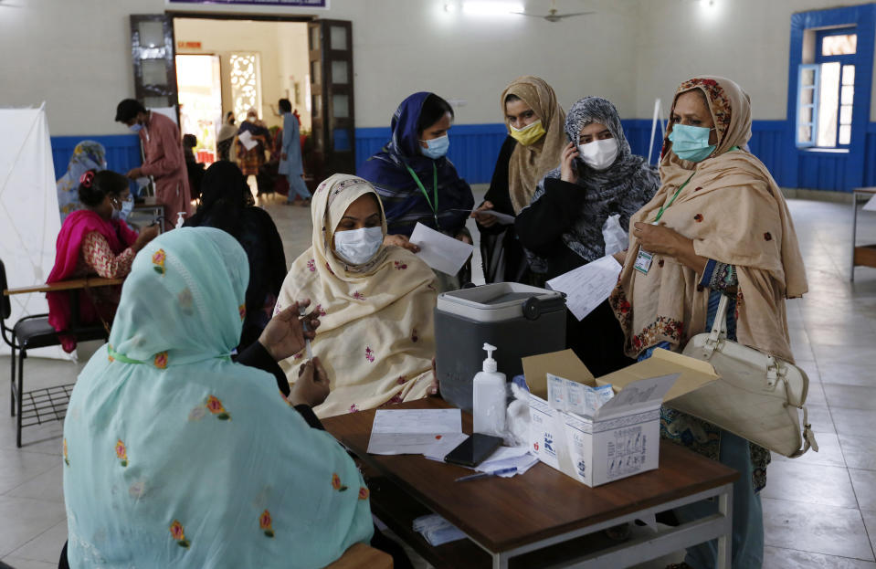 A teacher receives the first shot of the Sinovac coronavirus vaccine from a paramedic while in a vaccination center at a school in Lahore, Pakistan, Friday, May 28, 2021. (AP Photo/K.M. Chaudary)