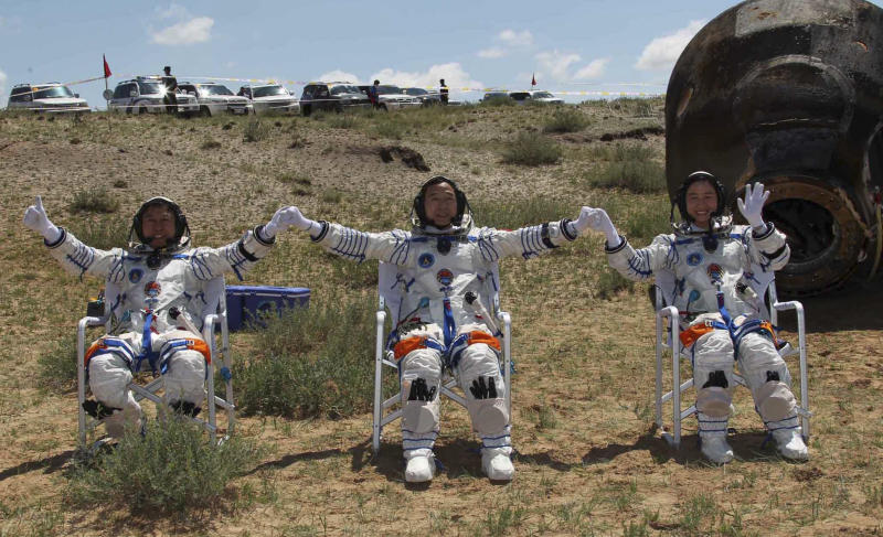 In this photo released by China's Xinhua news agency, Chinese astronauts, from left, Liu Wang, Jing Haipeng and Liu Yang, wave after coming out of the re-entry capsule, right, of Shenzhou-9 spacecraft in Siziwang Banner of north China's Inner Mongolia Autonomous Region Friday, June 29, 2012. The Chinese astronauts emerged smiling from the capsule that returned safely to earth Friday from a 13-day mission to an orbiting module that is a prototype for a future space station. (AP Photo/Xinhua, Wang Jianmin) NO SALES