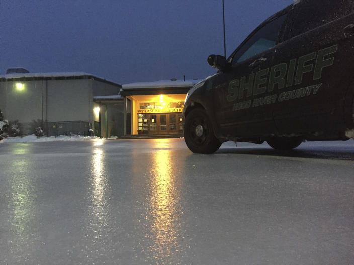 In this image provided by the Hood River County Sheriff, lights from a school reflect off the ice-coated parking lot in Hood River, Ore., Wednesday, Jan. 18, 2017. An ice storm shut down parts of major highways and interstates Wednesday in Oregon and Washington state and paralyzed the hardest hit towns along the Columbia River Gorge with up to 2 inches of ice coating the ground in some places.(Joel Ives/Hood River County Sheriff via AP)