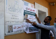 "An Islamic scholar posts defaced pictures of French President Emmanuel Macron at the entrance of the French Cultural center during a protest against the publishing of caricatures of the Prophet Muhammad they deem blasphemous, in Gaza City, Monday, Oct. 26, 2020. Arabic reads: ""Despite Macron's malice, we rise up to our Prophet"" and referring to criticism, ""Anything but God's messenger."" (AP Photo/Adel Hana)"