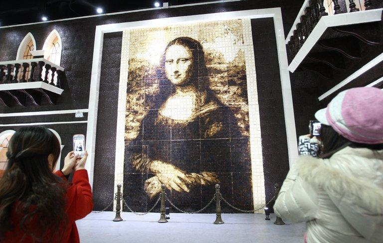 Visitors take photos on January 18, 2013 of a chocolate-made Mona Lisa painting, at the Chocolate Happy Land, in Shanghai. When it comes to chocolate the average Chinese -- having little sweet tooth or familiarity with it -- only consumes 100 grams a year, the equivalent of two Snickers bars