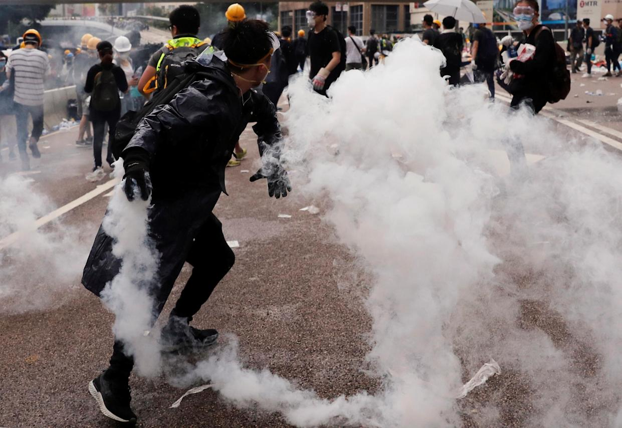 A protester throws a tear gas canister during a demonstration against a proposed extradition bill in Hong Kong, China June 12, 2019. REUTERS/Tyrone Siu