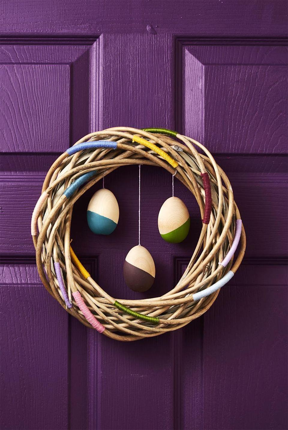 <p>Spruce up a craft grapevine wreath by wrapping colorful thread throughout. Hang a trio of decorated wooden eggs in the center to add fun movement when you open the door to greet guests. </p>