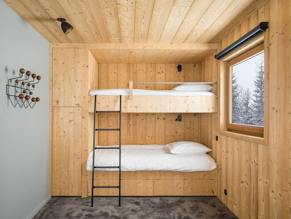 <p>This bunk room by Studio Razavi feelts like like a warm little mountain home cocoon, thanks to the built-in bunks that blend the ceiling and wall together so seamlessly. The plush velvet carpeting is cool in tone, picking up on the adjacent gray wall and balancing out the yellow base of the wood panels, but still brings so much tactile softness and warmth—an essential in a bedroom. </p>