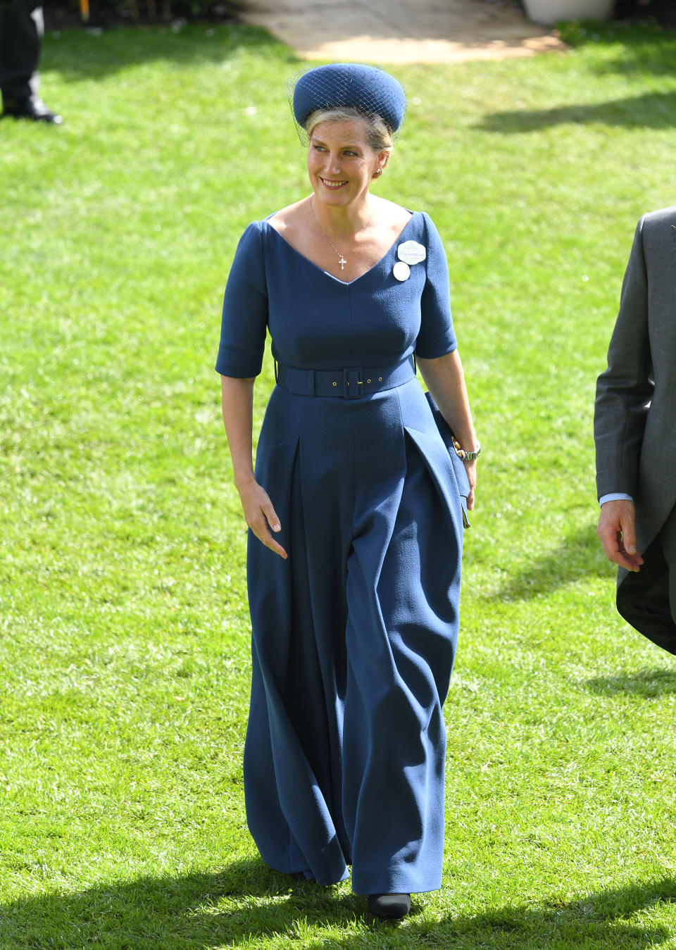 """Sophie, Countess of Wessex wore a bespoke belted navy jumpsuit by Emilia Wickstead - <a href=""""https://fave.co/2ZyI2Ib"""" rel=""""nofollow noopener"""" target=""""_blank"""" data-ylk=""""slk:available in red here"""" class=""""link rapid-noclick-resp"""">available in red here</a> with a <a href=""""https://fave.co/2ZFVaLD"""" rel=""""nofollow noopener"""" target=""""_blank"""" data-ylk=""""slk:Jane Taylor"""" class=""""link rapid-noclick-resp"""">Jane Taylor</a> veiled hat. <em>[Photo: PA]</em>"""