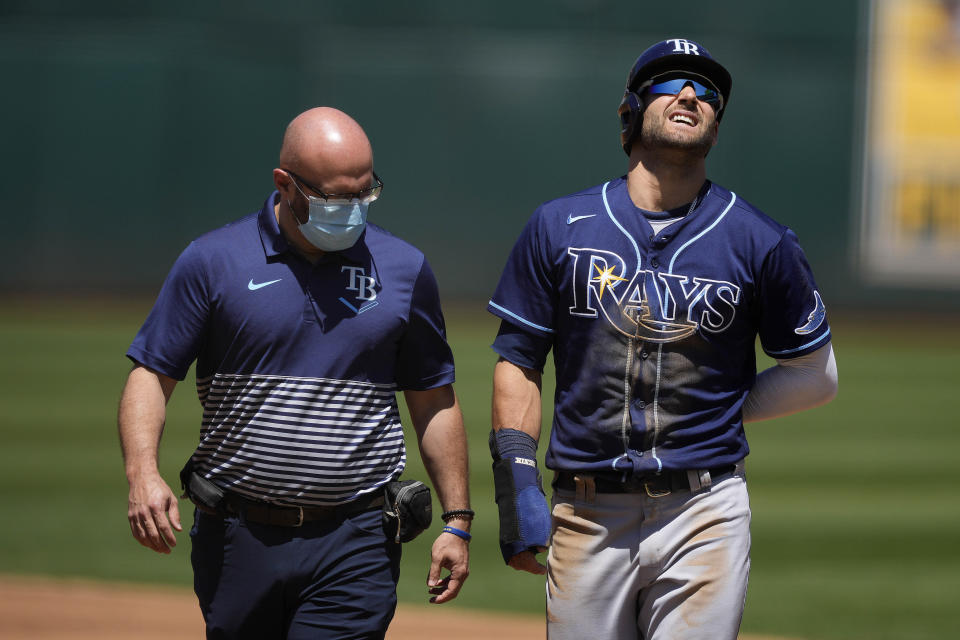 Tampa Bay Rays' Kevin Kiermaier, right, walks with a trainer back to the dugout after suffering an injury while stealing second base during the second inning of a baseball game against the Oakland Athletics, Saturday, May 8, 2021, in Oakland, Calif. (AP Photo/Tony Avelar)