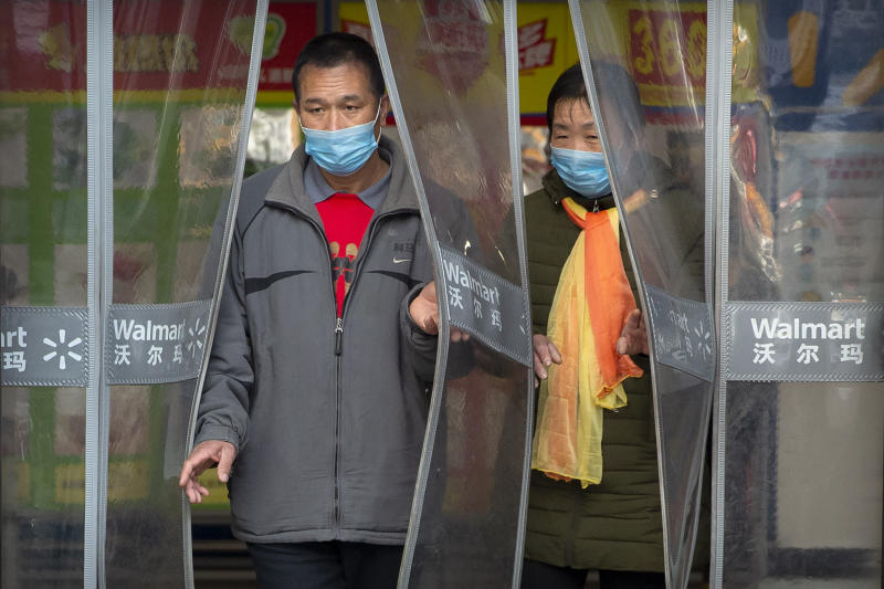 """People wear face masks as they leave a Walmart grocery store in Beijing, Saturday, Feb. 1, 2020. China's death toll from a new virus rose to 259 on Saturday and a World Health Organization official said other governments need to prepare for""""domestic outbreak control"""" if the disease spreads in their countries. (AP Photo/Mark Schiefelbein)"""