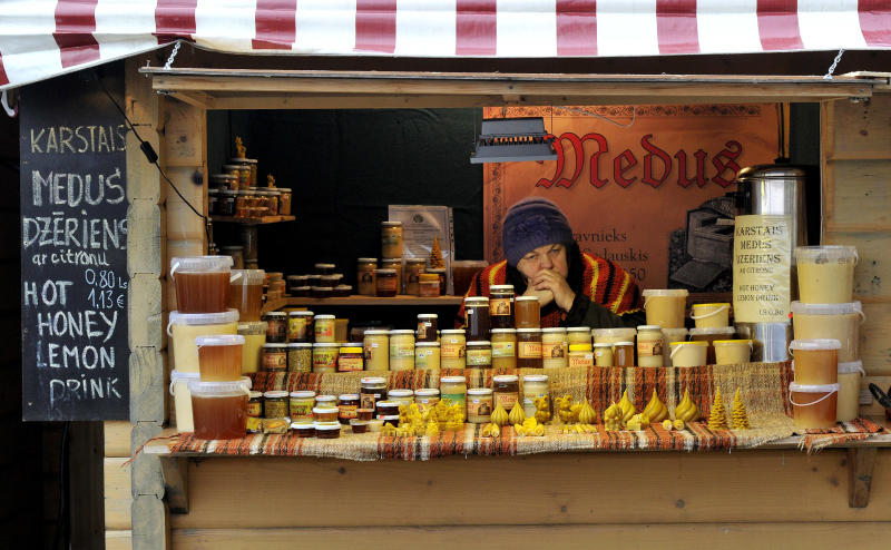 In this photo taken Friday, Dec. 27, 2013, an elderly woman sells honey at a Christmas market in downtown Riga, Latvia. When Latvia adopts the euro on Jan. 1, 2014 it will bring with it a banking sector that is swelling with suspicious money from Russia and the east _ just as the currency bloc is trying to clamp down on such havens. (AP Photo/Roman Koksarov)