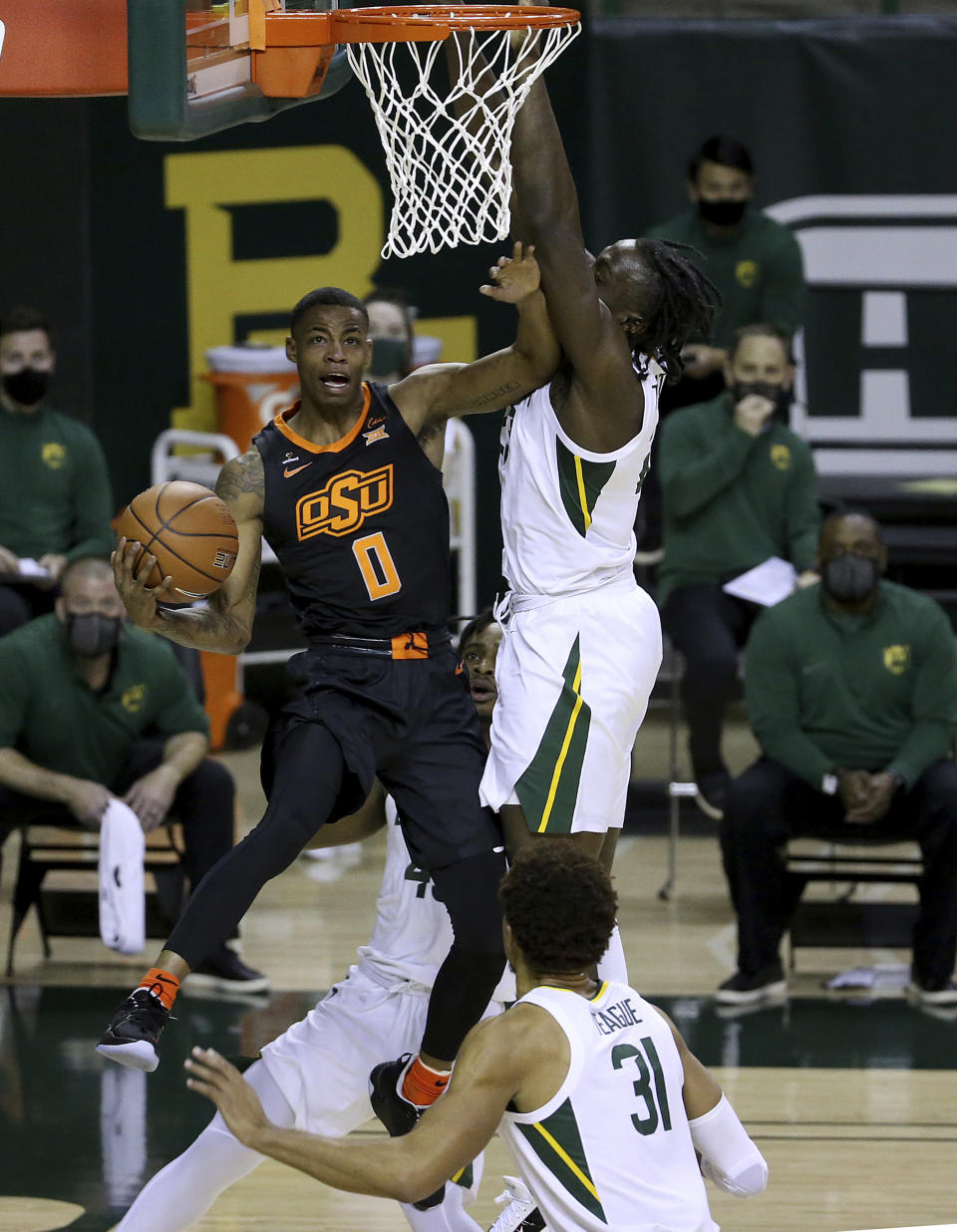 Oklahoma State guard Avery Anderson III (0) attempts a shot past Baylor forward Jonathan Tchamwa Tchatchoua (23) in the first half of an NCAA college basketball game, Thursday, March 4, 2021, in Waco, Texas. (AP Photo/Jerry Larson)