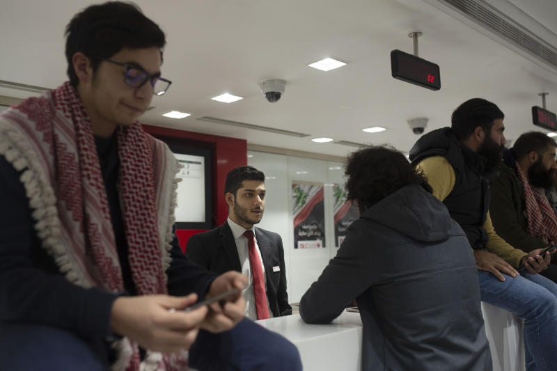 A Lebanese protester speaks with a bank teller during a sit-in at the Hamra branch of BLC Bank Dec. 28, 2019 in Beirut, Lebanon. Dozens of Lebanese protesters held a brief sit-in inside a bank in Beirut and another in the country's south on Saturday, part of their focus on banking policies they complain are inefficient and corrupt.(AP Photo/Maya Alleruzzo)