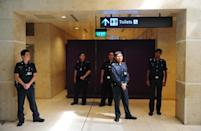 Police officers guard a holding area set up for family and friends of passengers from missing AirAsia Flight QZ8501 in Terminal 1 at Changi international airport in Singapore