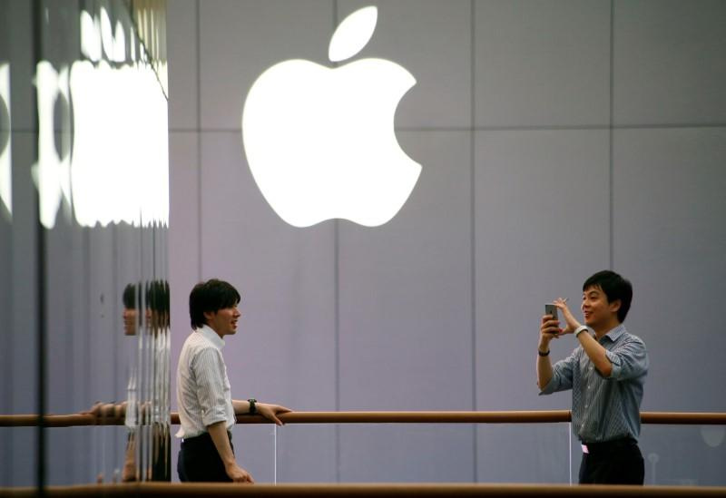 A man uses his phone to take pictures outside an Apple store in Beijing