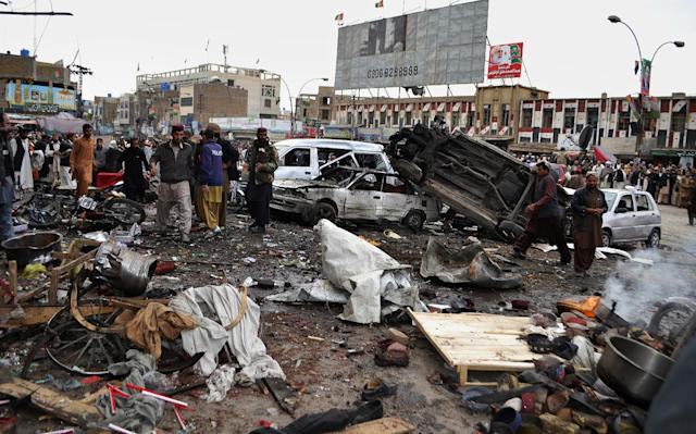 Pakistani police officers and local residents gather at the site of bomb blast in Quetta, Pakistan, Thursday, Jan. 10, 2013. A bomb targeting paramilitary soldiers killed scores of people in southwest Pakistan, officials said. (AP Photo/Arshad Butt)