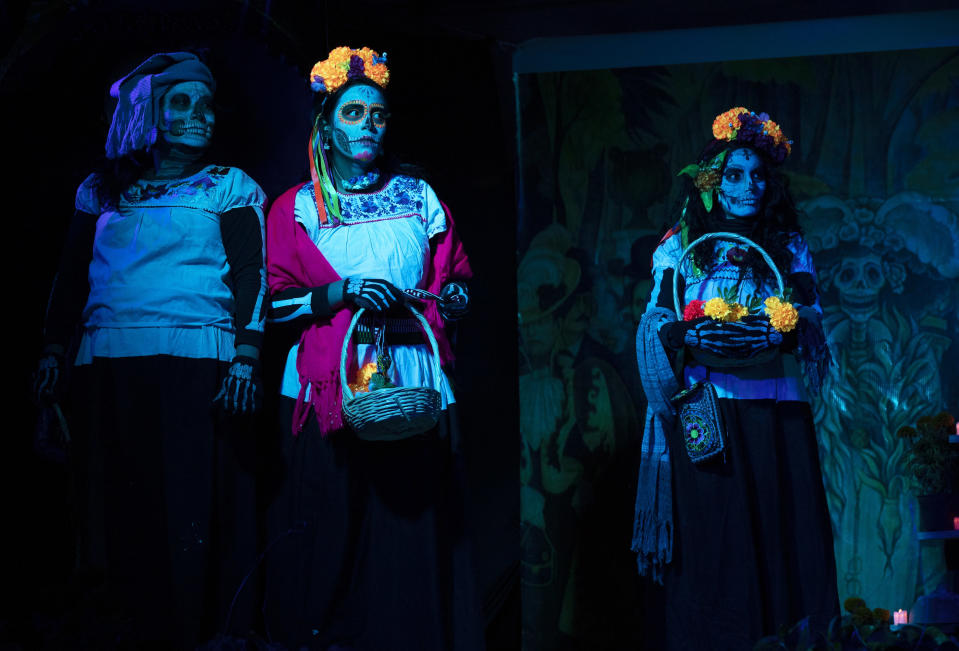 "Women dressed as ""Catrinas"" perform in a play promoting the upcoming Day of the Dead holiday, in the Xochimilco borough of Mexico City, Friday, Oct. 23, 2020. The iconic figures of skeletons with elegant wide-brimmed hats better known as Catrinas were created as satirical prints by Mexican artist Jose Guadalupe Posada sometime between 1910 and his death in 1913. (AP Photo/Marco Ugarte)"