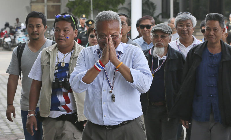 Anti-government protest leader Suthep Thaugsuban, center, along with his supporters greets the media as he arrives for a meeting with Thai armed forces at their headquarters in Bangkok, Thailand, Saturday, Dec. 14, 2013. The Thai military Supreme Command hosted the meeting wherein the leader of an anti-government protest group was given an opportunity to explain its goals and why they want to oust the caretaker government before upcoming elections. (AP Photo/Manish Swarup)