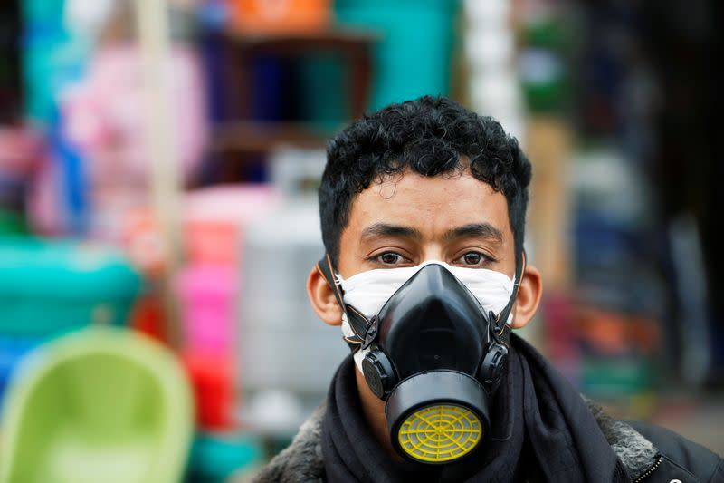 Man wears a protective face mask outside a shop amid concerns over the spread of the coronavirus disease (COVID-19), in Sanaa