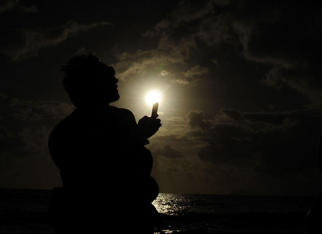 A spectator attempts to take a picture with his phone during the solar eclipse  on November 14, 2012 in Palm Cove, Australia.