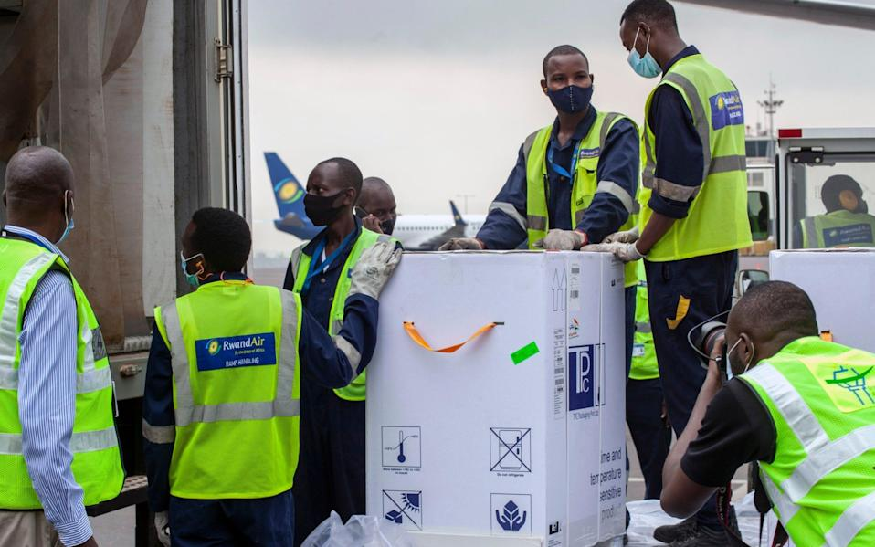 A shipment of vaccines is received by airport workers at the airport in Kigali, Rwanda - Muhizi Olivier/AP Photo