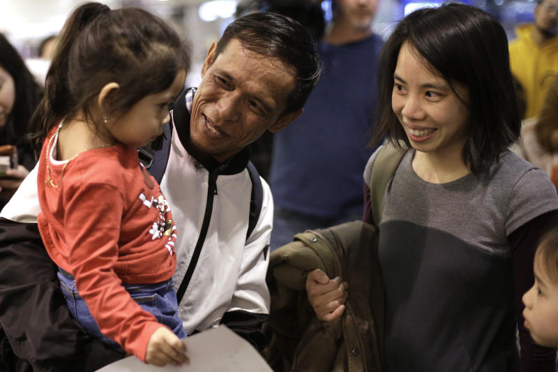 Thy Chea, of Lowell, Mass., center, originally of Cambodia, holds his daughter, left, as attorney Bethany Li, right, looks on Chea's arrival at Boston's Logan Airport, Wednesday, Feb. 26, 2020, after getting his green card reinstated last year. Chea is the fourth Cambodian refugee to be allowed back into the country after being deported, and just the first on the East Coast, according to Asian American organizations that have been fighting increased deportations of Southeast Asians under President Donald Trump. (AP Photo/Steven Senne)