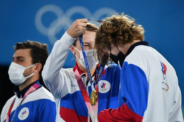Gold medalists Anastasia Pavlyuchenkova, center, and Andrey Rublev, right, of the Russian Olympic Committee put on their respective medals during the mixed doubles tennis medal ceremony on Aug. 1. (Photo: VINCENZO PINTO via Getty Images)