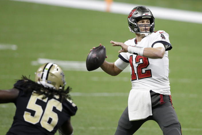 Tampa Bay Buccaneers quarterback Tom Brady (12) passes in front of New Orleans Saints outside linebacker Demario Davis (56) during the second half of an NFL divisional round playoff football game, Sunday, Jan. 17, 2021, in New Orleans. (AP Photo/Butch Dill)