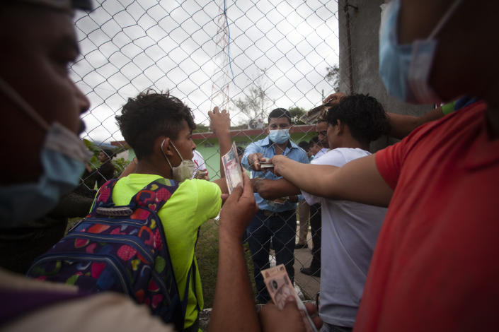 Migrants hoping to reach the distant U.S. border change money on the side of a highway, in Jocotan, Guatemala, Saturday, Jan. 16, 2021. Honduran migrants pushed their way into Guatemala Friday night without registering, a portion of a larger migrant caravan that had left the Honduran city of San Pedro Sula before dawn, Guatemalan authorities said. (AP Photo/Sandra Sebastian)