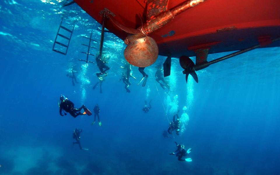 group of divers under red boat - Dive Worldwide Malta