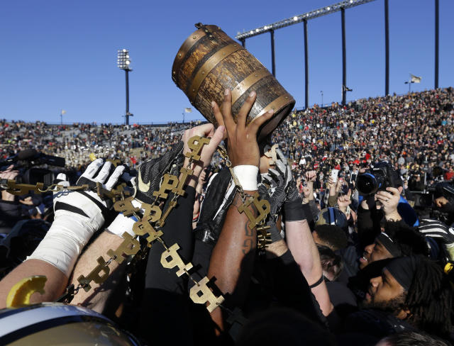 Purdue players celebrate with the Old Oaken Bucket after defeating Indiana 31-24. (AP)
