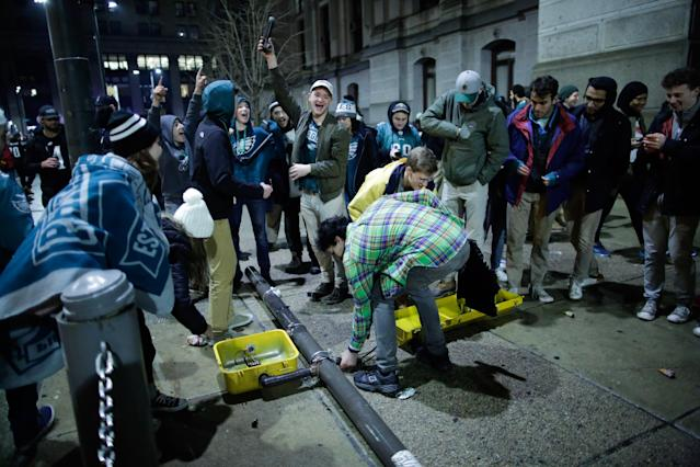 <p>People break a traffic light while celebrating the Philadelphia Eagles' victory in Super Bowl LII game against the New England Patriots on February 4, 2018 in Philadelphia, Pennsylvania..(Photo by Eduardo Munoz Alvarez/Getty Images) </p>