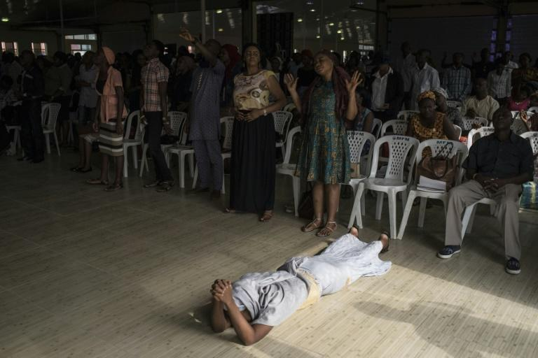 "A woman lies on the ground during prayer at a ""singles summit,"" one of several offered by hugely popular Pentecostal churches in Nigeria"