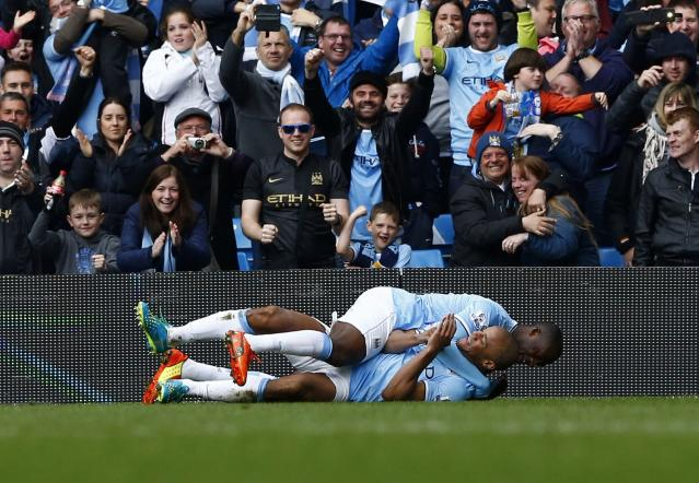 """Manchester City's captain Vincent Kompany (L) celebrates with teammate Yaya Toure after scoring against West Ham United during their English Premier League soccer match at the Etihad Stadium in Manchester, northern England May 11, 2014. REUTERS/Darren Staples (BRITAIN - Tags: SPORT SOCCER) FOR EDITORIAL USE ONLY. NOT FOR SALE FOR MARKETING OR ADVERTISING CAMPAIGNS. NO USE WITH UNAUTHORIZED AUDIO, VIDEO, DATA, FIXTURE LISTS, CLUB/LEAGUE LOGOS OR """"LIVE"""" SERVICES. ONLINE IN-MATCH USE LIMITED TO 45 IMAGES, NO VIDEO EMULATION. NO USE IN BETTING, GAMES OR SINGLE CLUB/LEAGUE/PLAYER PUBLICATIONS"""