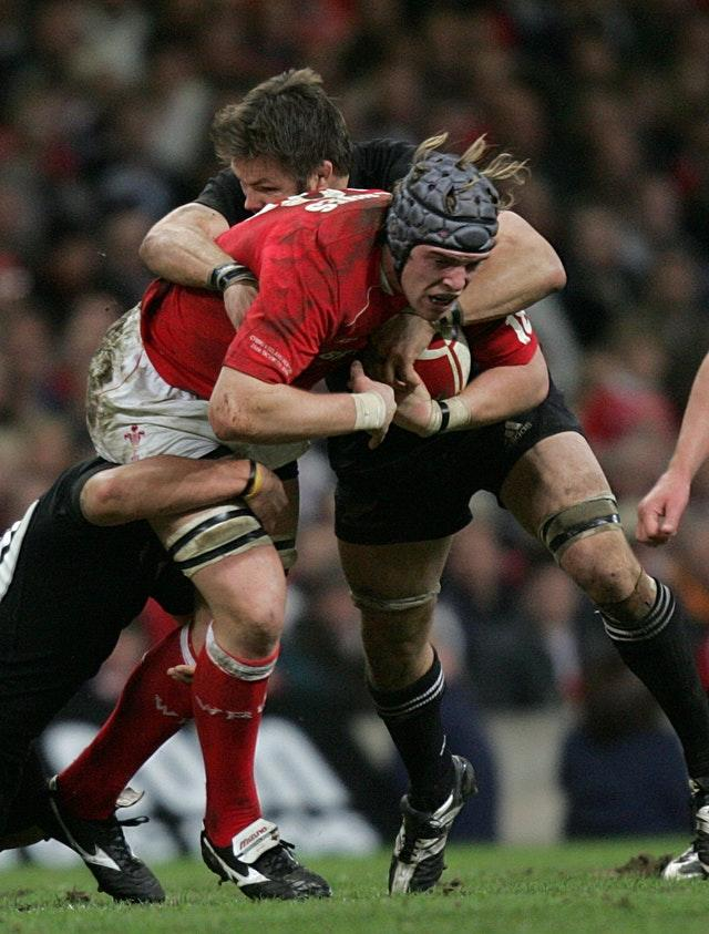 Alun Wyn Jones, left, is tackled by Richie McCaw