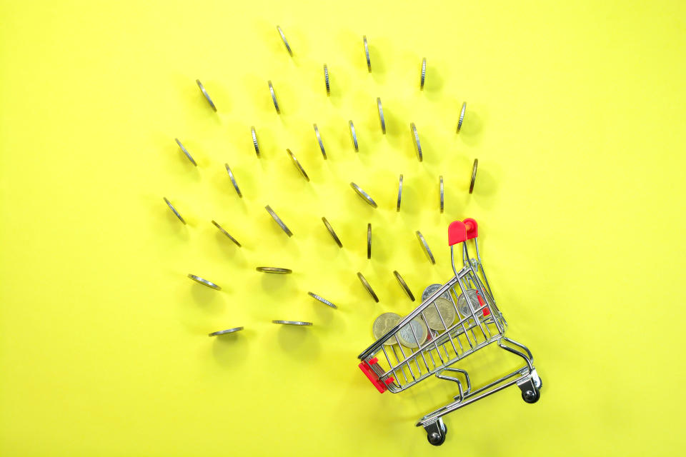 Concept of shopping and spending money. Money falling inside a shopping cart.