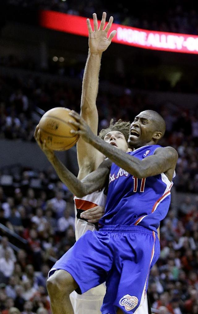 Los Angeles Clippers guard Jamal Crawford, right, goes to the basket against Portland Trail Blazers center Robin Lopez during the first half of an NBA basketball game in Portland, Ore., Thursday, Dec. 26, 2013. (AP Photo/Don Ryan)
