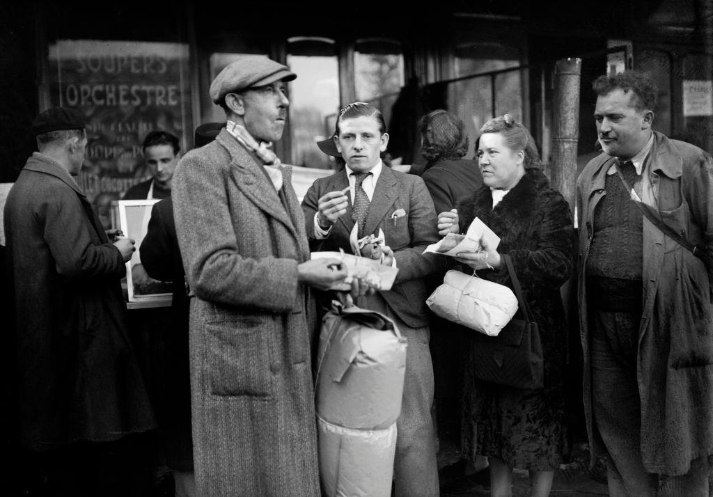 <p>A group of French men and women gather outside a Parisian shop for some <em>pomme frites</em>.</p>